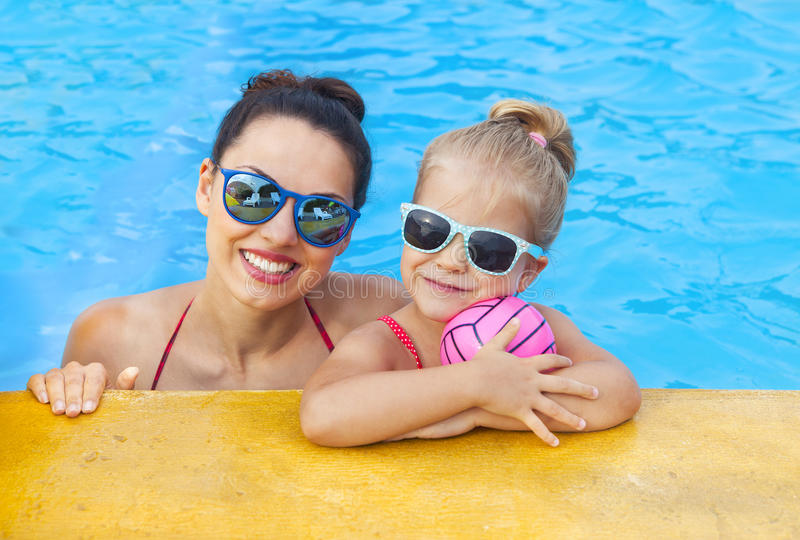 Happy mother and adorable little daughter having fun in a swimming pool royalty free stock image