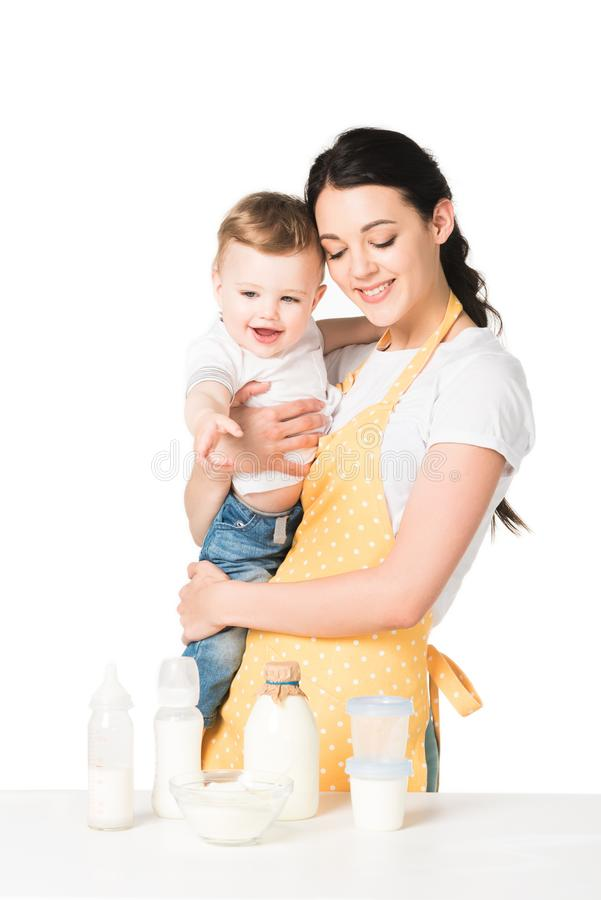 happy mother in apron holding baby boy at table with children food stock photography