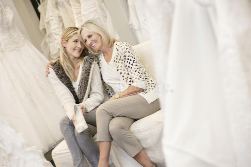 Happy Mother With Arm Around Her Daughter Sitting In Bridal Store Royalty Free Stock Image