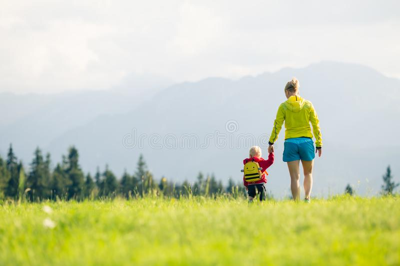 Happy mother with baby boy walking on green meadow royalty free stock image
