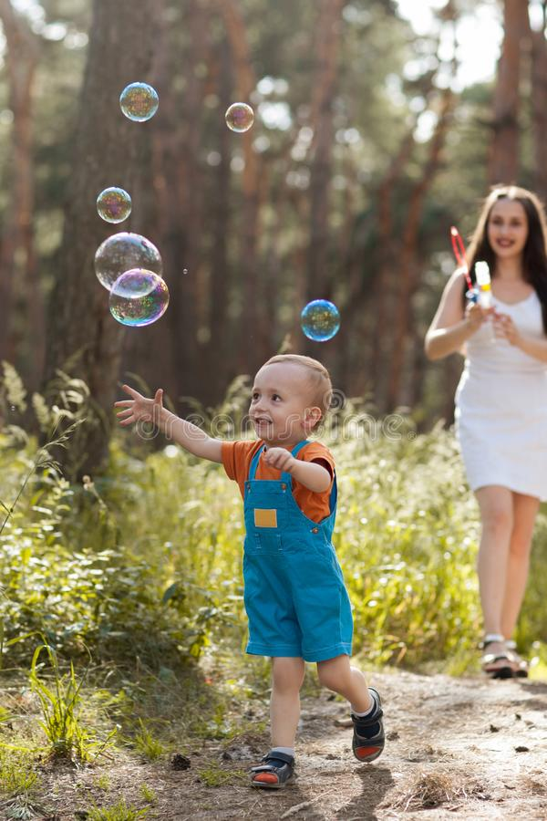 Happy mother baby bubble blower nature concept stock photography