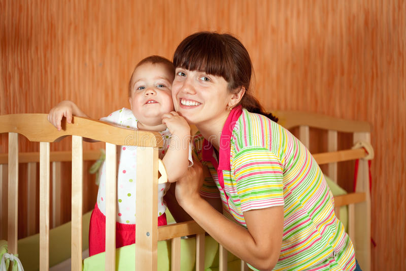 Happy mother with baby in crib stock image