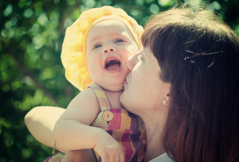 Happy mother with baby daughter. Against nature stock photo
