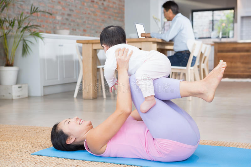 Happy mother and baby daughter exercising on mat. At home stock photography