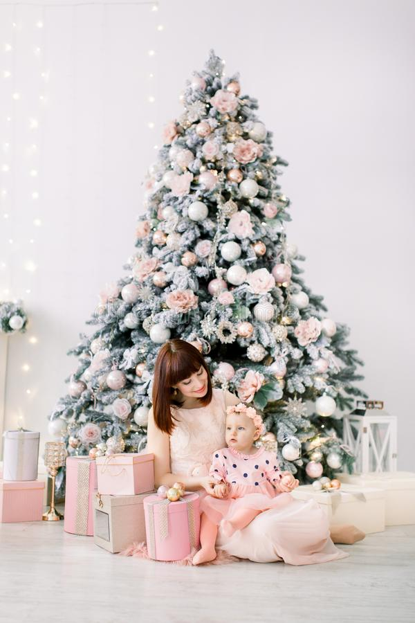 Happy mother and baby daughter playing home on Christmas holidays. New Year`s holidays. Toddler with mom in the stock image
