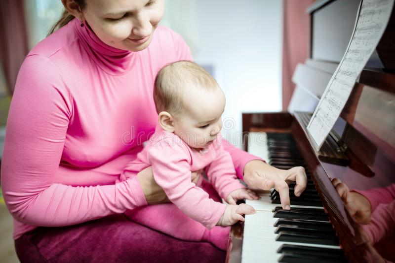 Happy Mother And Baby Daughter Are Playing Piano stock photos