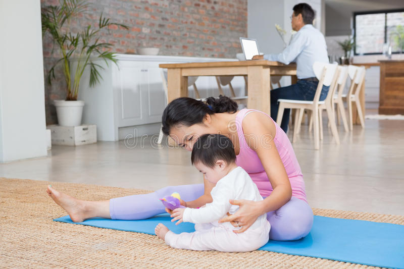 Happy mother and baby daughter sitting on exercising mat. At home royalty free stock photos