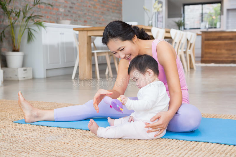 Happy mother and baby daughter sitting on exercising mat. At home royalty free stock photography