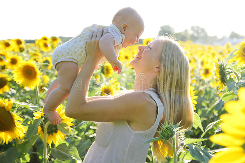 happy mother and baby daughter in sunflower field stock. Black Bedroom Furniture Sets. Home Design Ideas