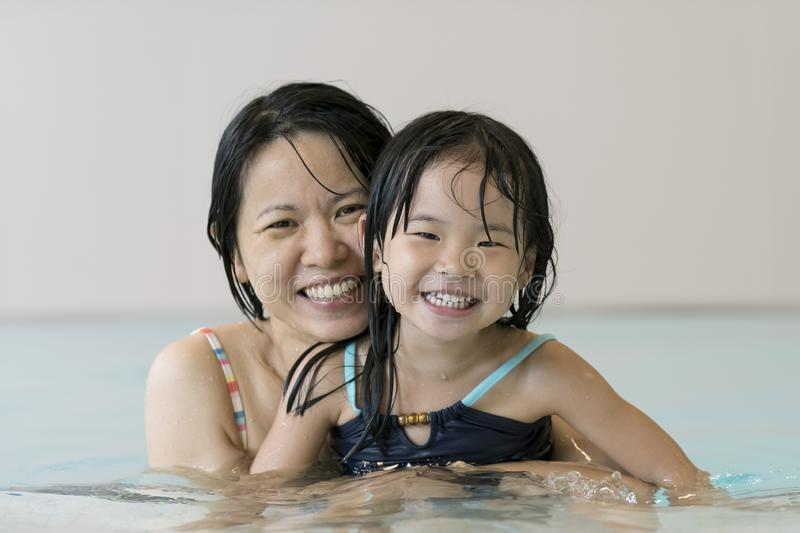 Happy mother and baby daughter at swimming pool royalty free stock images