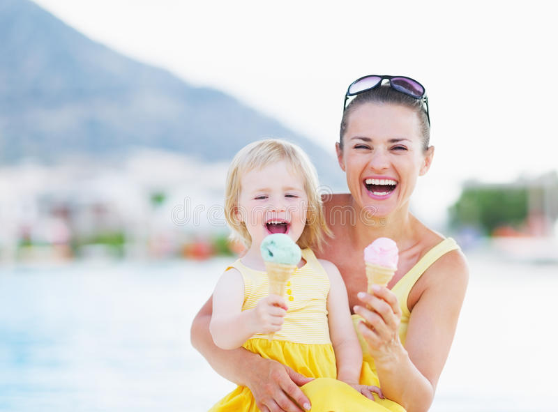 Happy mother and baby eating ice cream stock images