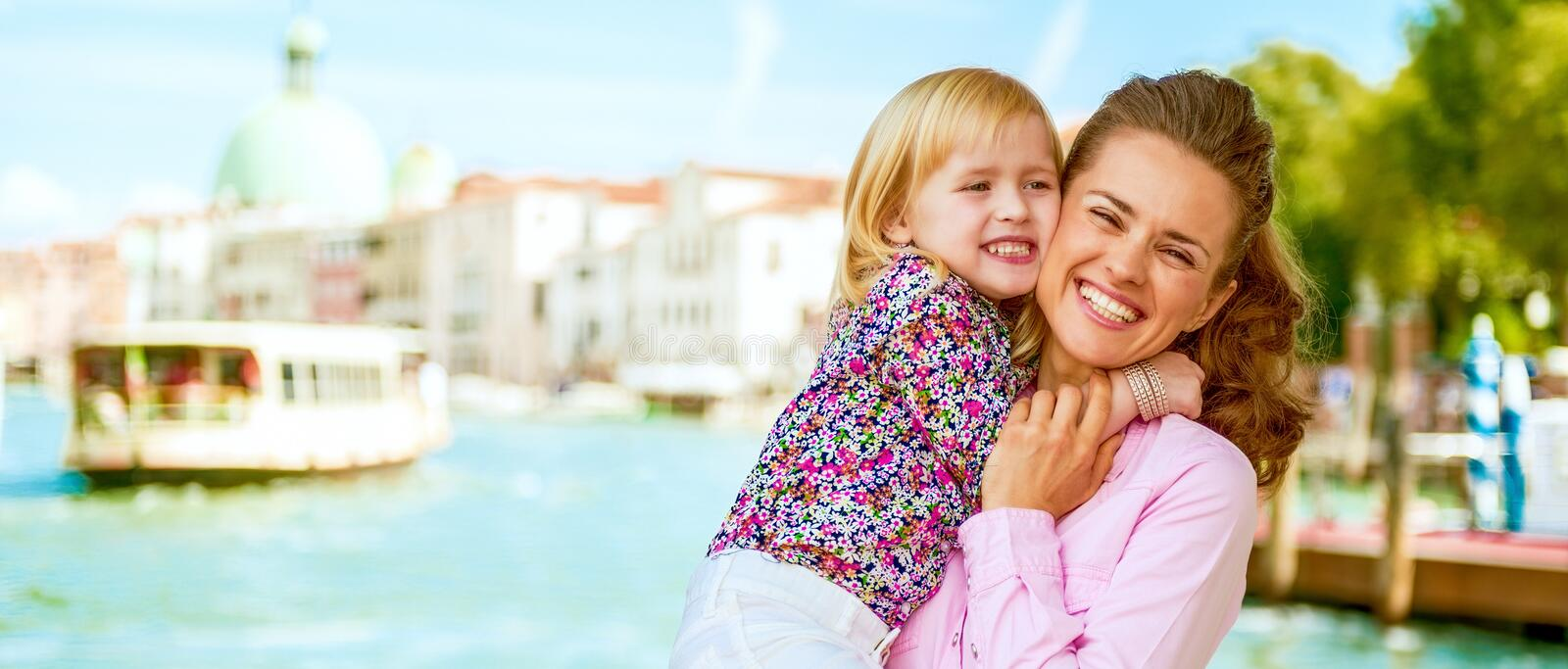 Happy mother and baby hugging on grand canal embankm stock photo