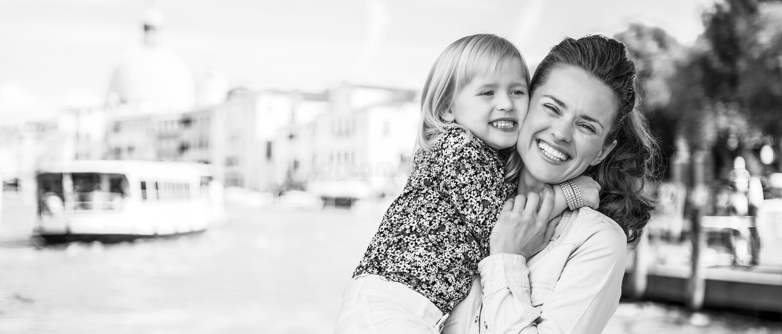 Happy mother and baby hugging on grand canal embankm stock photos