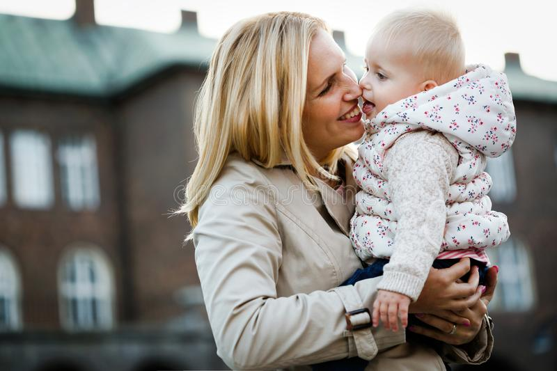 Happy mother and baby kissing, laughing and hugging in nature outdoors royalty free stock photo