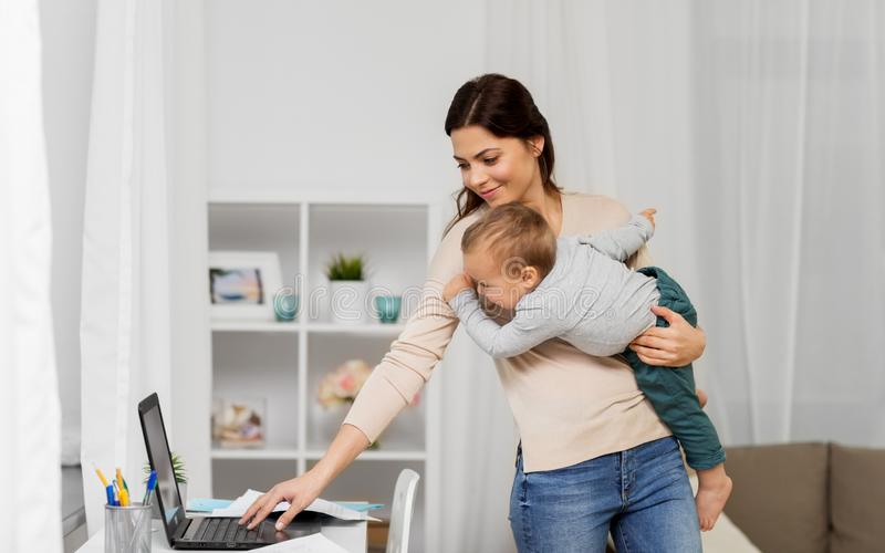 Happy mother with baby and laptop working at home royalty free stock photos