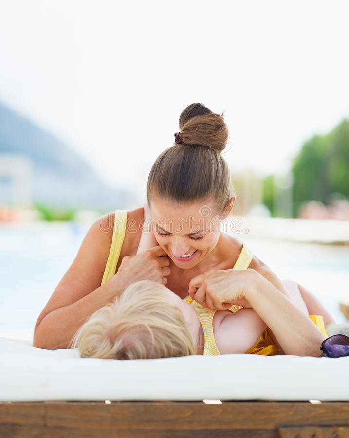 Happy mother and baby playing at poolside. High-resolution photo royalty free stock photo