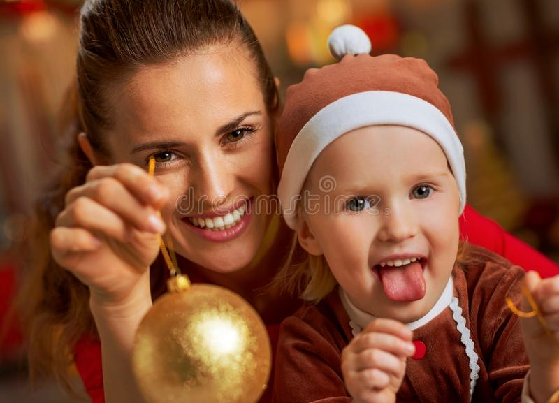 Mother and baby showing christmas ball stock image