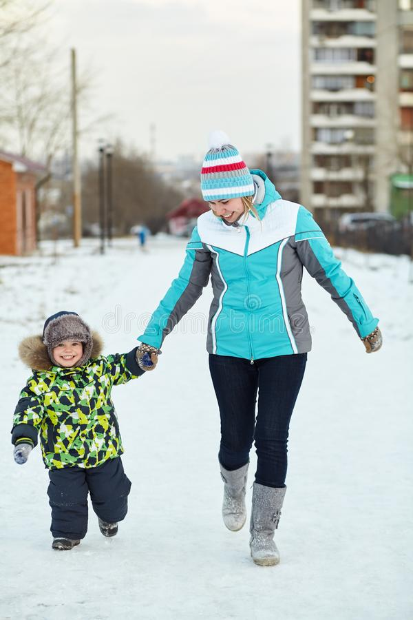 Happy mother and baby walking in winter. family outdoors. cheerful mom with her child. royalty free stock image