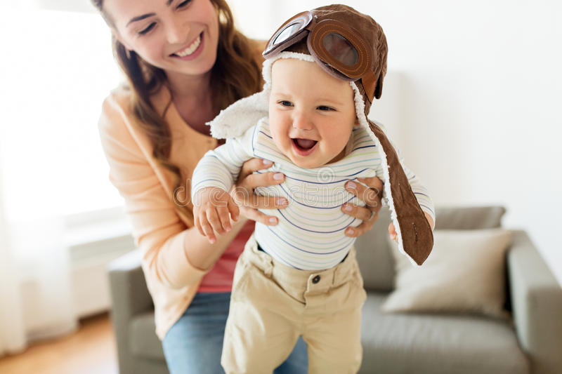 Happy mother with baby wearing pilot hat at home. Family, child and motherhood concept - happy smiling young mother playing with little baby wearing pilot hat at stock photos