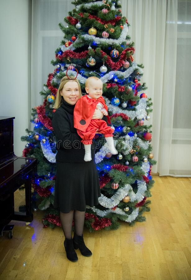Happy mother with child in Christmas background near decorated tree royalty free stock photography
