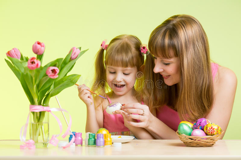 Happy mother and child daughter prepare to Easter holiday with brush coloring eggs royalty free stock photo