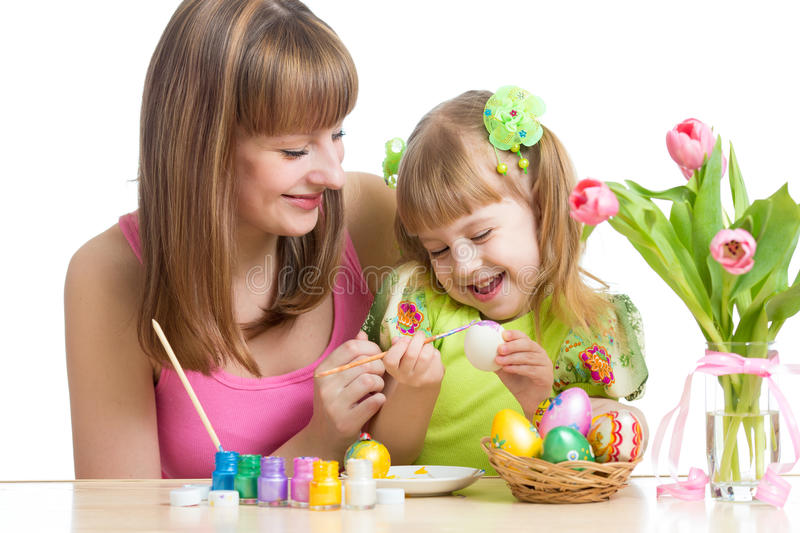 Happy mother and child daughter preparing to easter holiday and with brush coloring eggs royalty free stock images