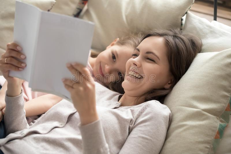 Happy mother and child daughter reading book laughing in bed stock photo