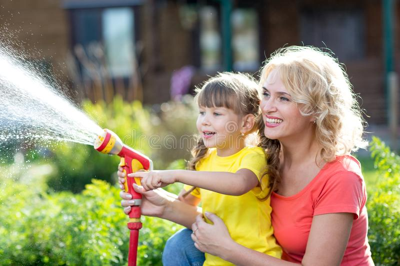 Happy mother and child watering in domestic garden. Happy mother and child daughter watering in domestic garden royalty free stock photos