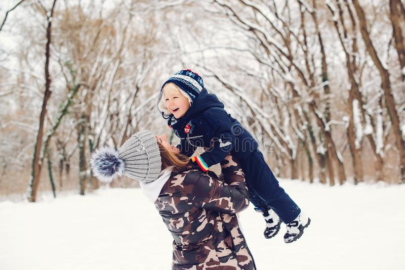 Happy mother and child having fun on snowy winter walk in nature. Frost winter season. Happy loving family. Winter and christmas stock image
