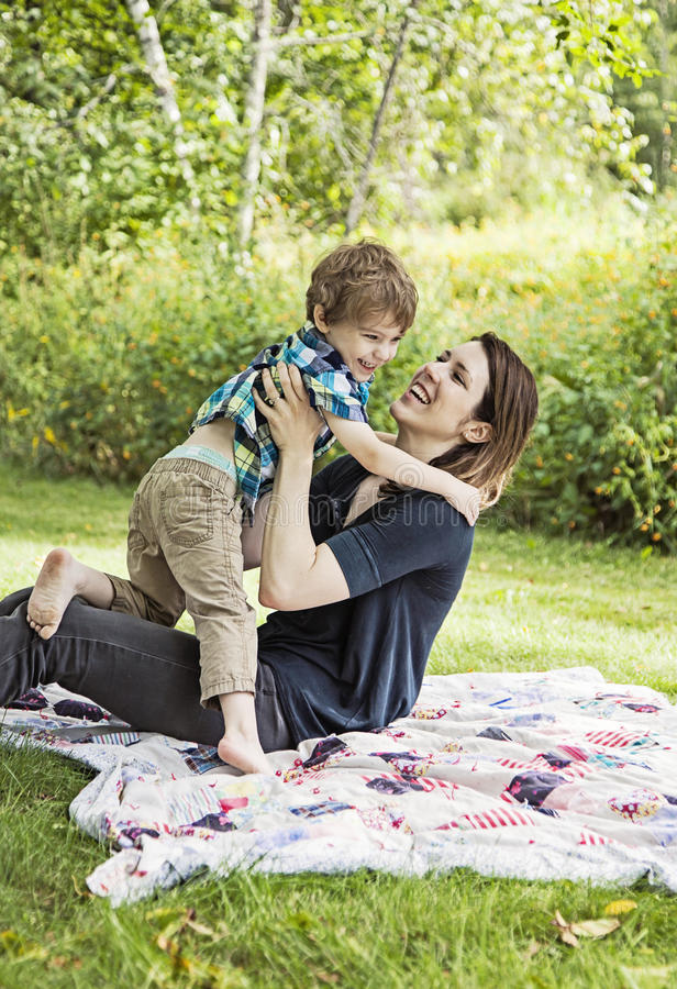 Happy mother and child. Mother and son playing and laughing on blanket outdoors stock photography