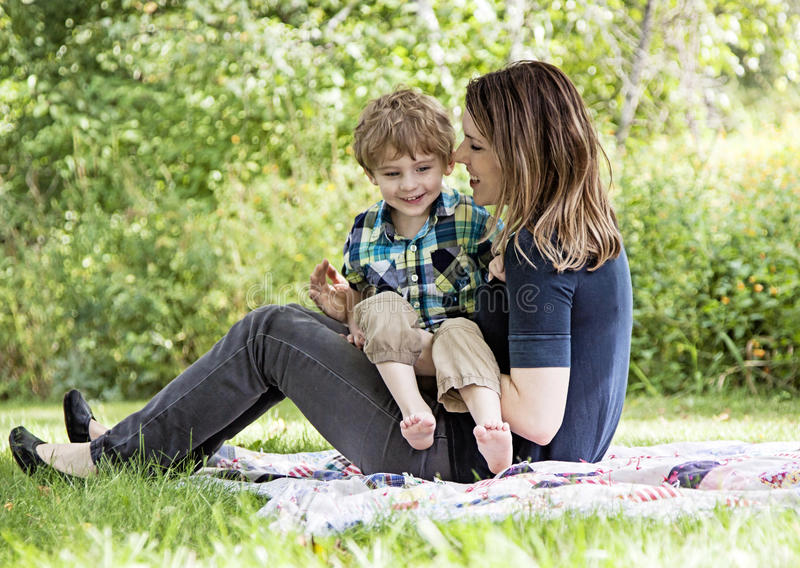 Happy mother and child. Mother and son playing and laughing on blanket outdoors royalty free stock photo