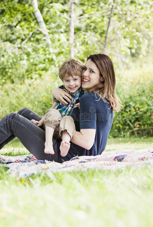 Happy mother and child. Mother and son playing and smiling on blanket outdoors royalty free stock images