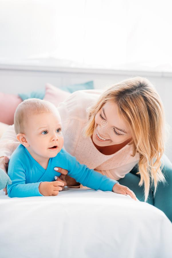 Happy mother and child spending time together on bed. At home royalty free stock image