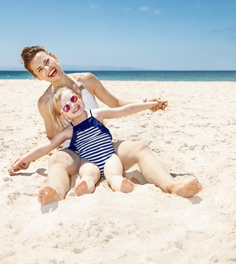 Happy mother and child in swimsuits at sandy beach playing royalty free stock photography