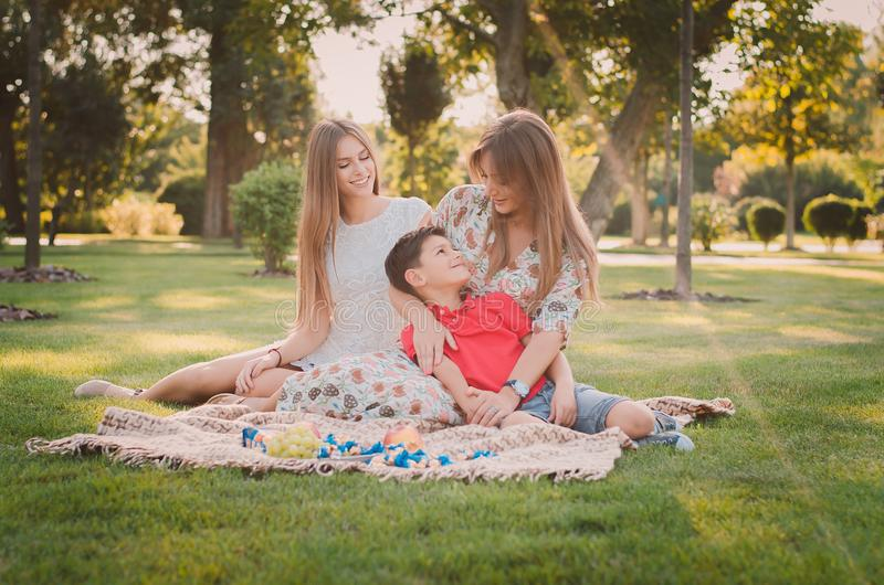 A happy mother and children are having fun in the park on a warm summer day. They`re on the lawn in the park. royalty free stock image