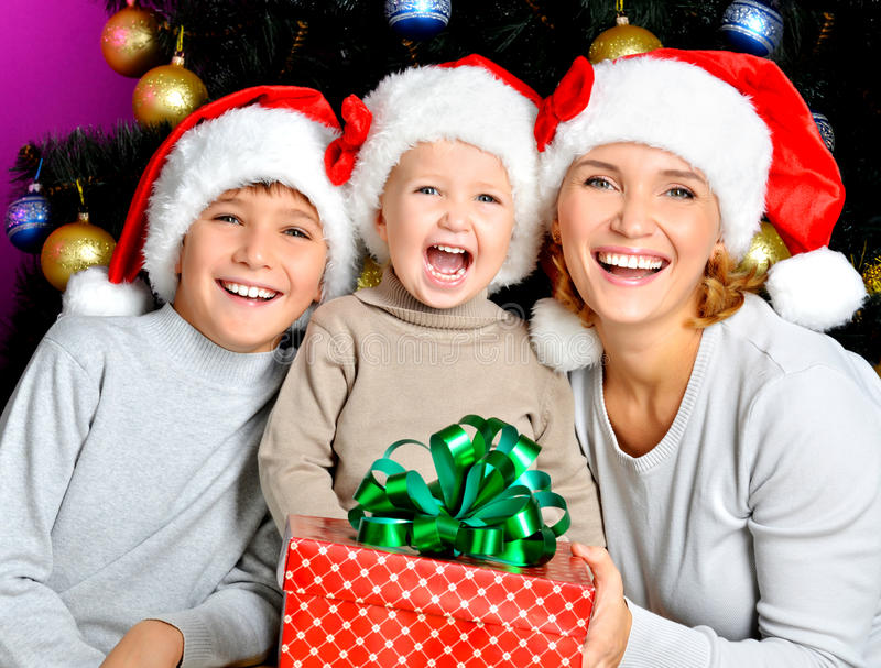 Happy mother with children holds the new year gift royalty free stock photography
