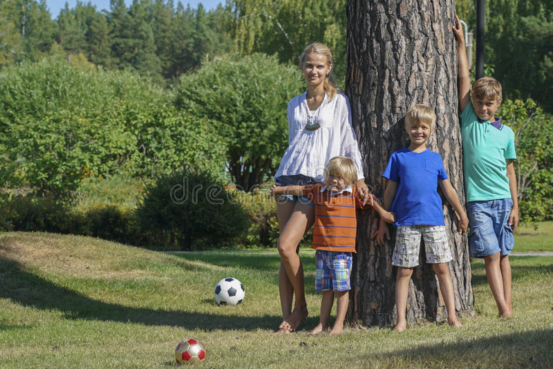Happy mother with children standing under the big tree. Portrait of happy mother with three boys standing under the big tree in the park stock image