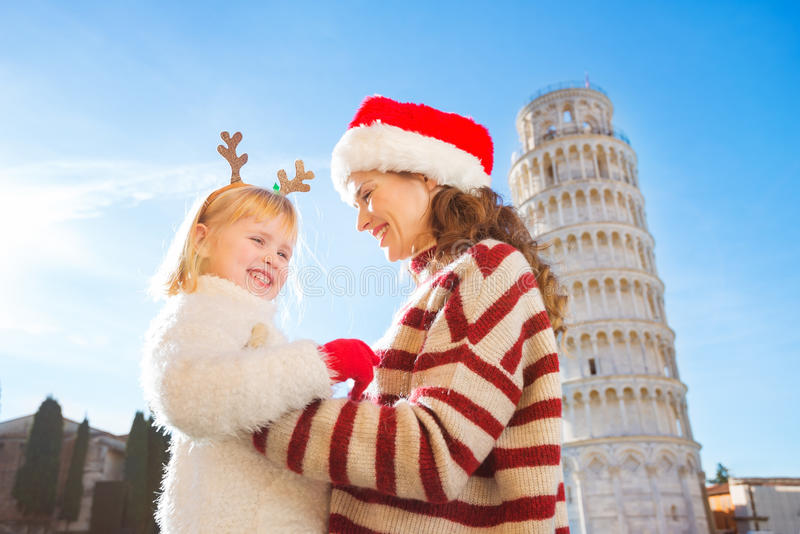 Happy mother in Christmas hat and daughter. Christmas in Pisa. Smiling mother in Christmas hat and cosy sweater and daughter wearing funny reindeer antlers stock photos