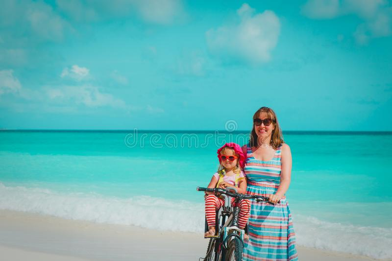 Happy mother with cute little baby girl bike at beach royalty free stock photos