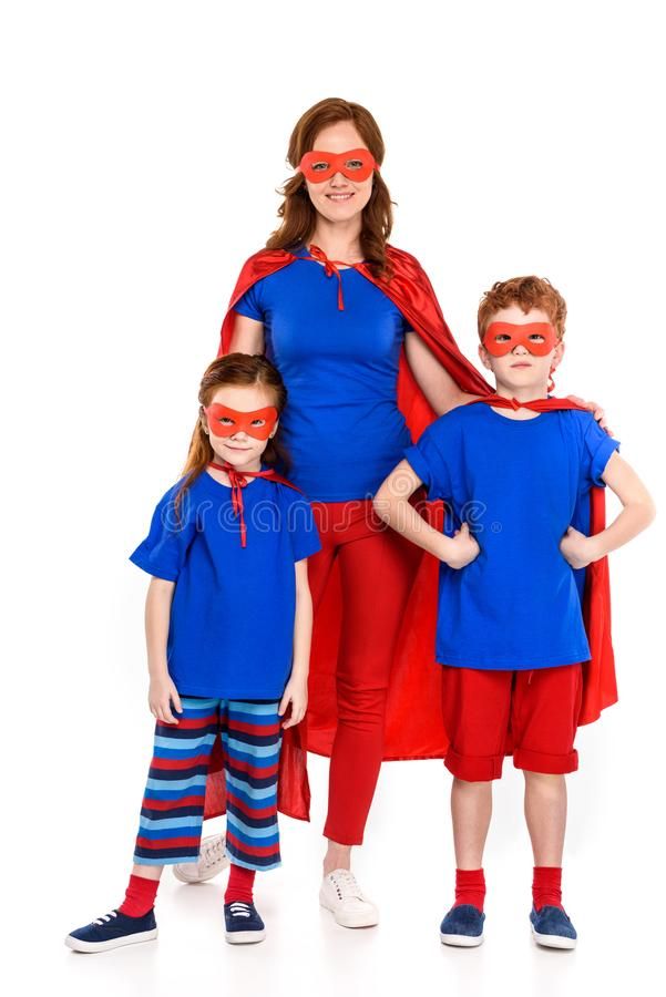 happy mother with cute little kids in superhero costumes standing together and smiling at camera stock photo