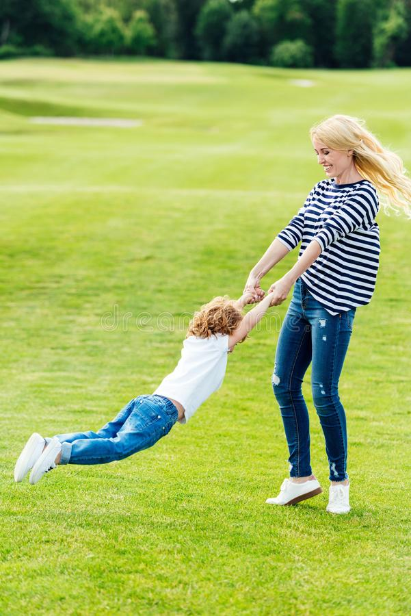 happy mother with cute little son playing on green meadow royalty free stock images