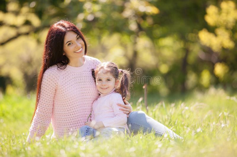 Happy mother and daughter in the autumn park. Beauty nature scene with family outdoor lifestyle. Happy family resting together on stock photography