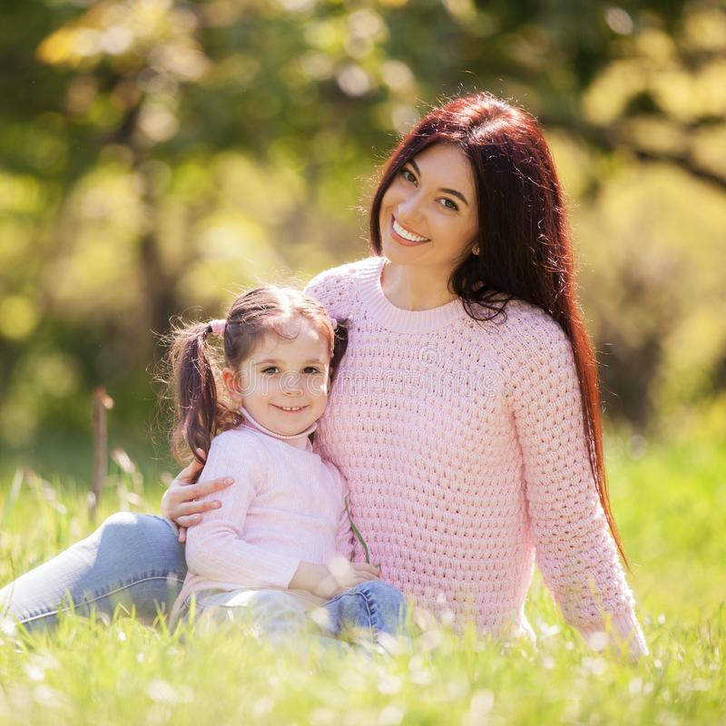 Happy mother and daughter in the autumn park. Beauty nature scene with family outdoor lifestyle. Happy family resting together on stock photo
