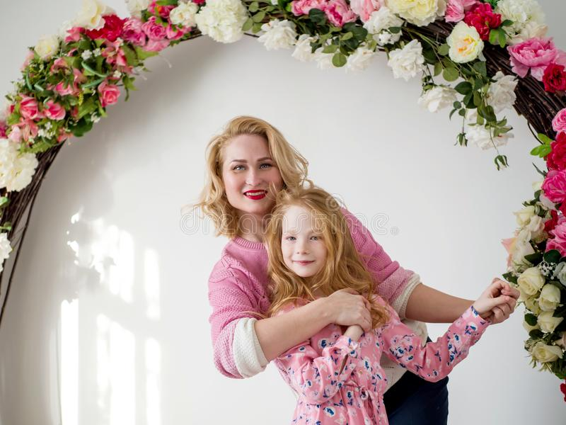 Happy mother and daughter on a background of flowers. A happy family stock photography