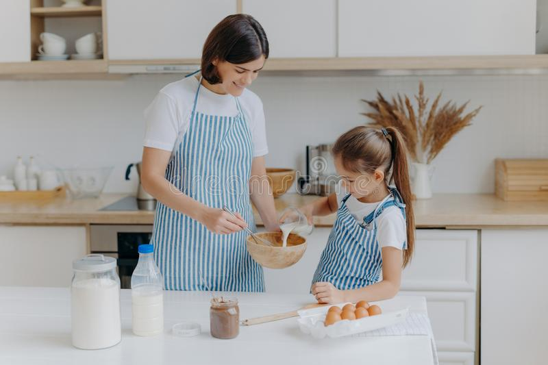 Happy mother and daughter bake together in kitchen, use different ingredients, wear aprons, stand against kitchen interior, girl royalty free stock photography