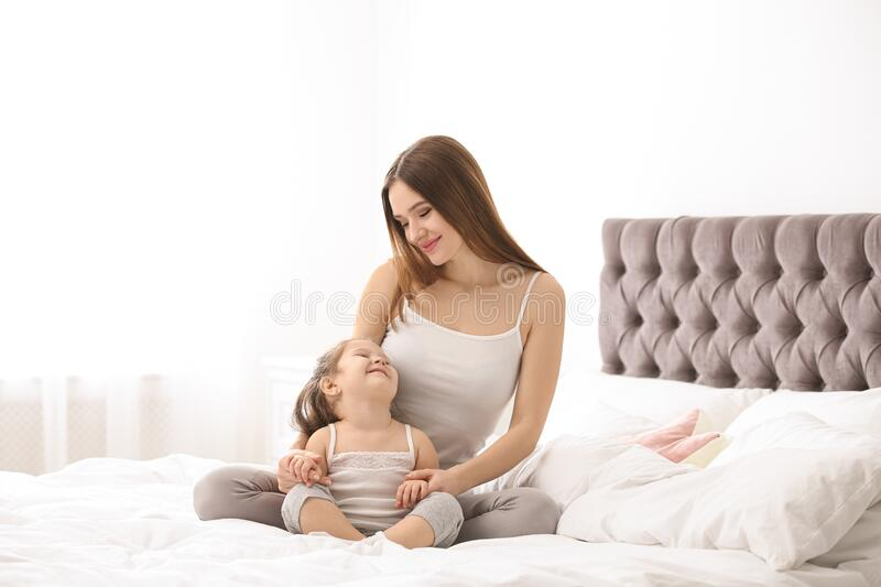 Happy mother with daughter in bedroom stock images