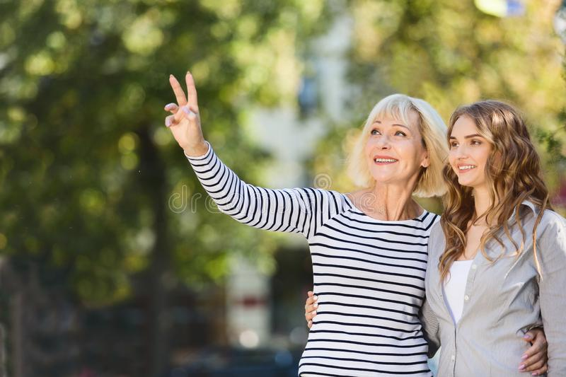 Happy mother and daughter bird watching in park royalty free stock photography
