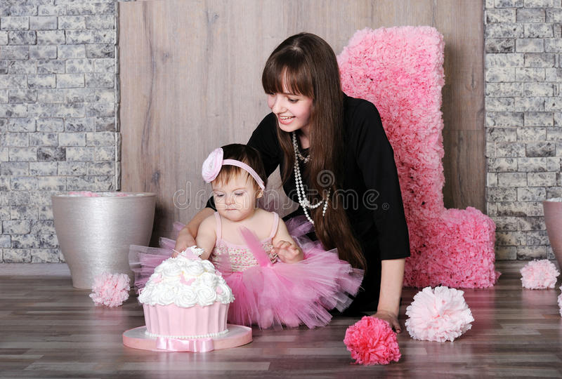 Happy mother and daughter celebrating first birthday. Happy mother and daughter celebrating first birthday, mother teach little girl eat a cake stock images