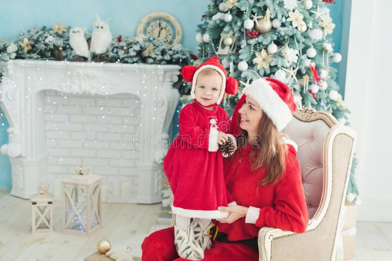 Happy mother and daughter in Christmas hats and in red dress sitting in armchair near fireplace and Christmas tree with gifts stock photo