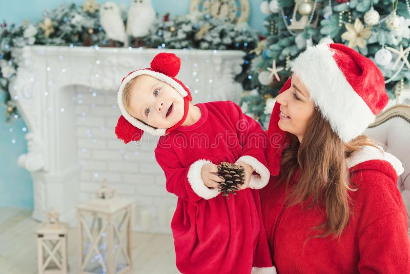 Happy mother and daughter in Christmas hats and in red dress sitting in armchair near fireplace and Christmas tree with gifts stock image